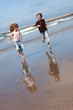 Catch me if you can. Happy kids running by the ocean Royalty Free Stock Images