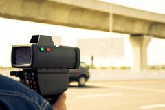 Catch speeding drivers. With a radar gun, vintage color style Royalty Free Stock Images