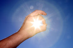 Catch the Sun. Hand catching the sun on blue sky Royalty Free Stock Images