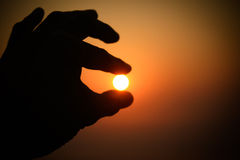 Catch the Sun. Finger catching the sun in the morrning royalty free stock photo