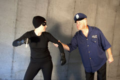 Catch a Thief. Woman dressed as a thief being caught by a man dressed as a police officer Royalty Free Stock Photos