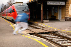 Catch the train. A man (blurred silhouette) is running across railway tracks on a train station to catch the nearby standing train - on the billboard is the Royalty Free Stock Photo