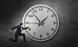 Catch up with time. Concept of time with funny businessman running in a hurry Royalty Free Stock Photo