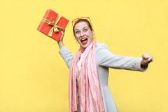 Catch your gift! Young adult crazy woman swung and wants to throw off your gift box, isolated on yellow background. Studio shot royalty free stock photos