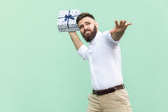Catch your gift! Young adult man swung and wants to throw off your gift box, isolated on light green background. Studio shot Stock Image