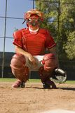 Catcher Gesturing A Hand Sign. Baseball catcher crouches as gestures a hand sign royalty free stock photos