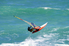 Catching Air Windsurfing on Oahu Hawaii. Stock Photo of a windsurfer in mid-air while windsurfing at Diamond Head Beach Park in Hawaii.  Photo by Paul Topp Royalty Free Stock Photography