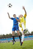 Catching ball. Two footballers jumping and looking at ball on grass-field during game Stock Images
