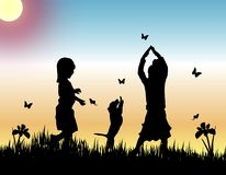 Catching Butterflies. Silhouettes of two children an dog catching butterflies at sunset Stock Photo