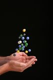 Catching falling marbles against a black background Stock Image