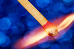 Matchstick Catching fire II. Closeup of wooden match catching fire on blue background Royalty Free Stock Photos