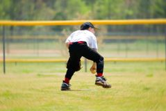 Catching Ground Ball/Blur. Little league baseball player making a catch on a ground ball; with radial blur added stock photography