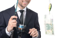 Catching money with fishing rod. Businessman catching money with fishing rod isolated Royalty Free Stock Image