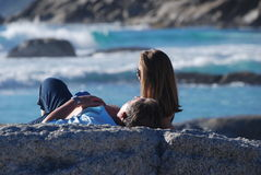 Catching rays. Couple relaxes while enjoying afternoon sun at Noordhoek Beach, cape Town Stock Photo