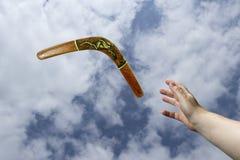 Catching returning painted boomerang Royalty Free Stock Photos
