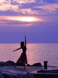 Catching the sky. Young woman standing at ballerina pose, sunset at the background stock photography