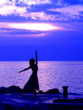 Catching the sky. Young woman standing at ballerina pose, sunset at the background Stock Image