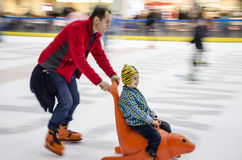 Speeding up. Little boy enjoys gliding on the rink while he is being pushed by his father, during normal public opening hours, at the Afi Palace Cotroceni Mall