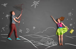 Catching stars. Happy valentines love story concept of a romantic couple catching stars with a butterfly net against chalk drawings background of a night sky Royalty Free Stock Photography