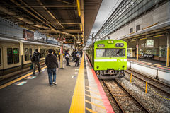 Catching A Train In Japan. Commuters waiting to board a train at a relatively quiet station in Tokyo, Japan Royalty Free Stock Photo