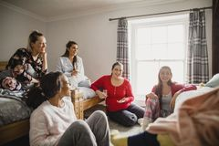 Catching Up with Friends. Small group of female friends relaxing and talking while enjoying a girls night in. They are sitting in a bedroom in their pyjamas royalty free stock photography