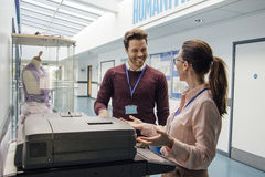 Catching Up At The Printer. Two teachers are talking while standing at a printer in the school hall royalty free stock images