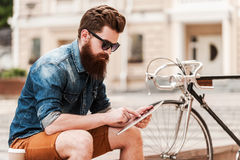 Catching up on some news. Handsome young bearded man holding digital tabletwhile sitting near his bicycle outdoors stock photo