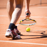 Catching up tennis ball from orange sand Stock Image