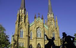 Catedral da basílica do St Dunstan e a estátua de bronze de dois pais da confederação no dia ensolarado em Charlottetown imagens de stock