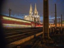 Catedral de Colonia en la noche con un tren que pasa a través imagen de archivo