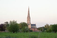 Catedral de Salisbúria e prado verde na noite imagens de stock