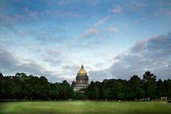 Catedral entre árboles con el cielo hermoso y la hierba verde Imágenes de archivo libres de regalías