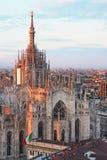 Catedral principal e bandeira italiana no por do sol em Milão fotos de stock royalty free