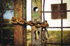 Catena arrugginita del ferro sul portone con la grande serratura davanti all'immagine di casa fotografie stock libere da diritti