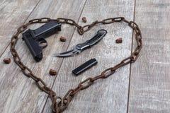 Catena arrugginita sotto forma di un cuore in cui una pistola su un fondo di legno Vista superiore da un angolo immagine stock libera da diritti