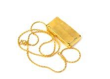 Catena dell'oro e barra di oro su fondo bianco Fotografia Stock