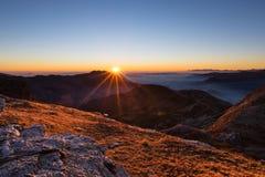 Catena montuosa al tramonto, lampadina con lo sprazzo di sole, alpi italiane Immagine Stock