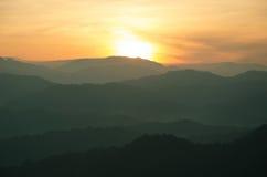 Catena montuosa con luce e foschia dorate immagine stock