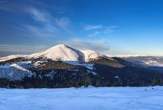 Catena montuosa coperta di neve con la foresta al fondo di una montagna Fotografie Stock