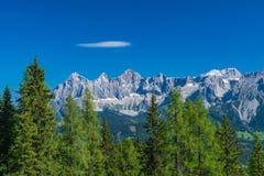 Catena montuosa di Hohe Dachstein in Austria con gli alberi verdi in Fotografie Stock