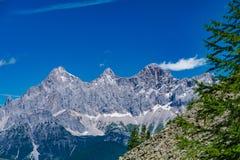 Catena montuosa di Hohe Dachstein in Austria con gli alberi verdi in Fotografie Stock Libere da Diritti