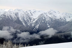 Catena montuosa innevata oltre un campo di Snowy fotografia stock