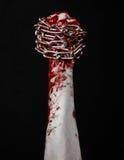 Catena sanguinosa della tenuta della mano, catena sanguinosa, tema di Halloween, fondo nero, isolato Immagini Stock