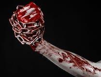 Catena sanguinosa della tenuta della mano, catena sanguinosa, tema di Halloween, fondo nero, isolato Immagine Stock