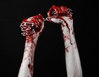 Catena sanguinosa della tenuta della mano, catena sanguinosa, tema di Halloween, fondo nero, isolato Fotografie Stock Libere da Diritti