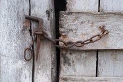 Catena sulla vecchia porta di legno fotografie stock