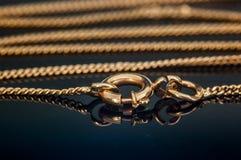 Catenaccio o chiusura della catena della collana dell'oro chiusa sulla tavola di vetro di riflessione Fotografia Stock