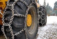 Catene di neve sulle grandi rotelle dello slittatore Fotografie Stock Libere da Diritti