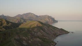 Catene montuose pittoresche Siluetta dell'uomo Cowering di affari Bello paesaggio con il mare di vista video d archivio