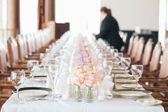 Caterer sets Table. Long Row of Pink Flowers. A caterer sets the table for an event. The table is adorned with wine glasses, fine china, and a long row of pink Royalty Free Stock Photos